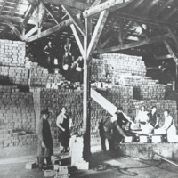 Men using machinery to assist in the stacking Red Cross parcels in a barn